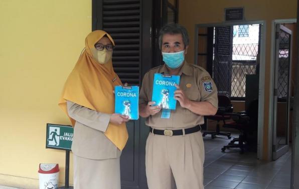 Kabid Pembinaan dan Pengembangan Perpustakaan Provinsi Babel Abu Hapas bersama Waka SMAN 4 Pangkalpinang Eldawati memperlihatkan buku Corona untuk Perpustakaan Provinsi.
