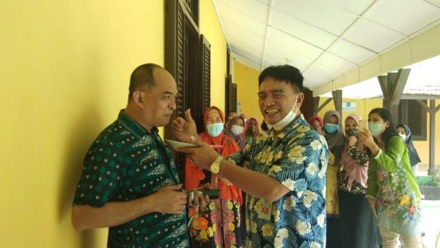 Kepala DKPUS Babel Rakhmadi memberikan potongan tumpeng pertama kepada Sekretaris DKPUS Babel Agus Afandi.
