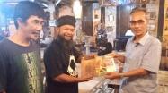 Asyraf Suryadin Kadis DKPUS Babel menyerahkan sumbangan buku rakyat ke Janggut, Pemilik Café Janggut Belitung, Kamis (27/5/2021) malam.